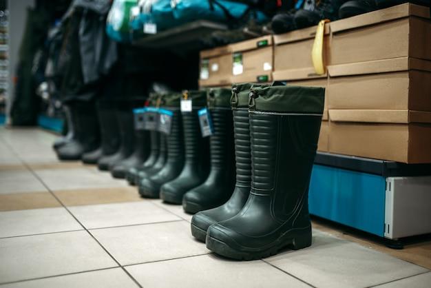 Fila di stivali di gomma nel negozio di pesca