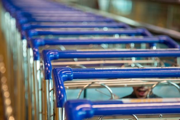Fila delle maniglie blu del primo piano dei carrelli della spesa