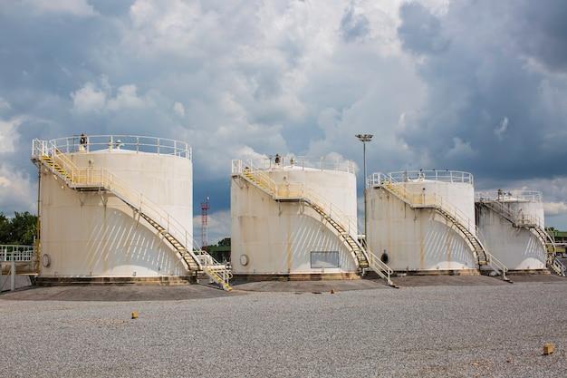 La fila di piccoli serbatoi bianchi per la stazione di servizio e il pezzo di ricambio della raffineria.