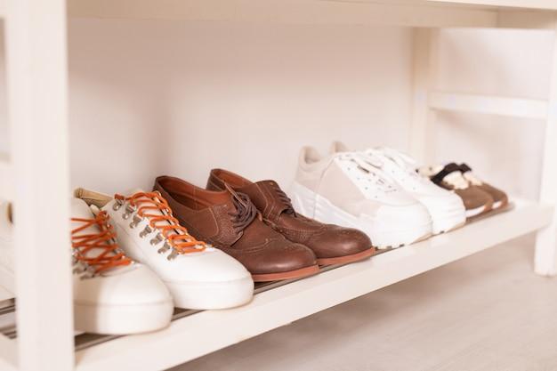 Fila di calzature sportive e casual da parete sul ripiano inferiore bianco sopra il pavimento della stanza domestica, corridoio in un appartamento o studio