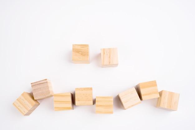 Una fila di dieci blocchi di legno vuoti su una priorità bassa bianca con copyspace per il vostro testo, lettere o numeri.