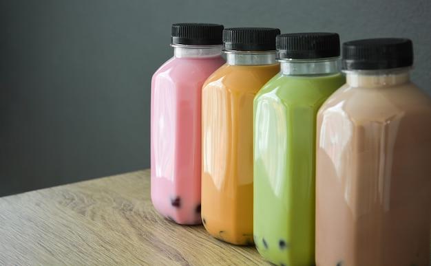 Una fila di vari bobble tea in bottiglie di plastica su un tavolo di legno con sfondo di colore nero