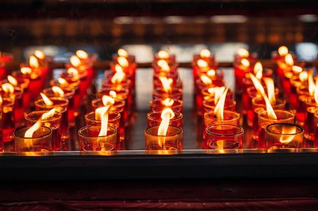 Fila di candela rossa religiosa votiva con fiamma in vetro al tempio cinese