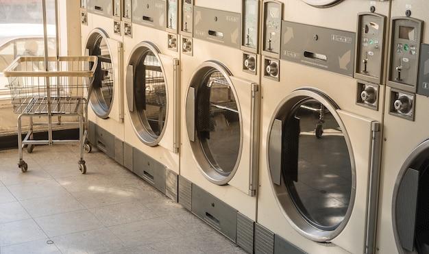 Fila della lavatrice del business della lavanderia nel negozio pubblico.