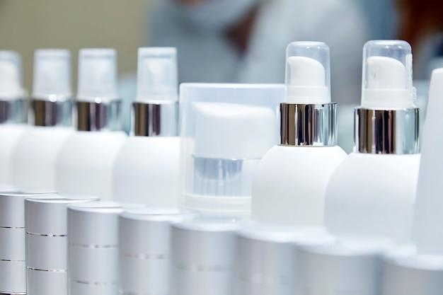 Fila di bottiglie vuote bianche con prodotti cosmetici