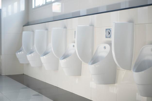Una fila di orinatoi in ceramica bianca per uomini in bagno.