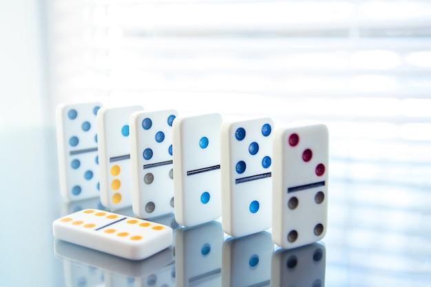 Fila di domino bianchi sulla superficie dello specchio
