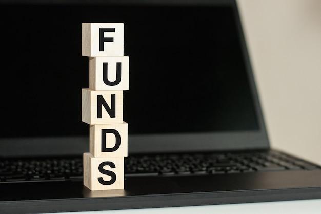 Una fila di cubi di legno con una parola fondi scritta in caratteri neri si trova su una tastiera nera. fondi testo scritto su blocco di legno sulla tastiera del computer su sfondo nero. concetto di affari.