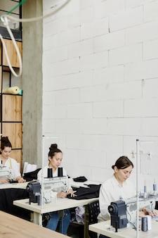Fila di giovani stilisti seduti alle scrivanie e utilizzando macchine da cucire elettriche mentre lavorava alla nuova collezione stagionale