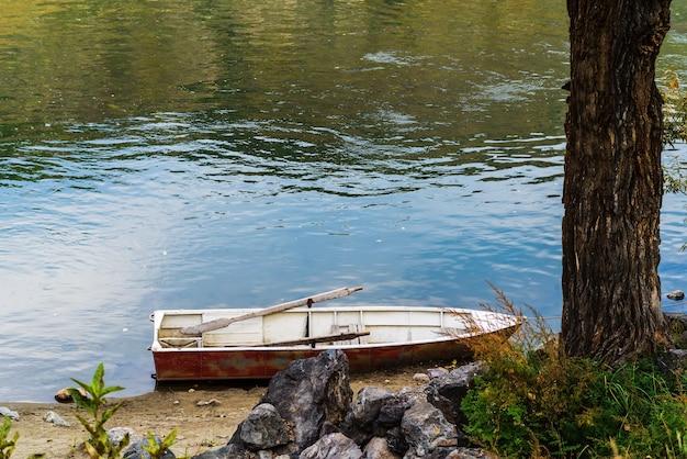 Barca a remi ormeggiata alla riva del fiume. fiume chulyshman, altai, russia