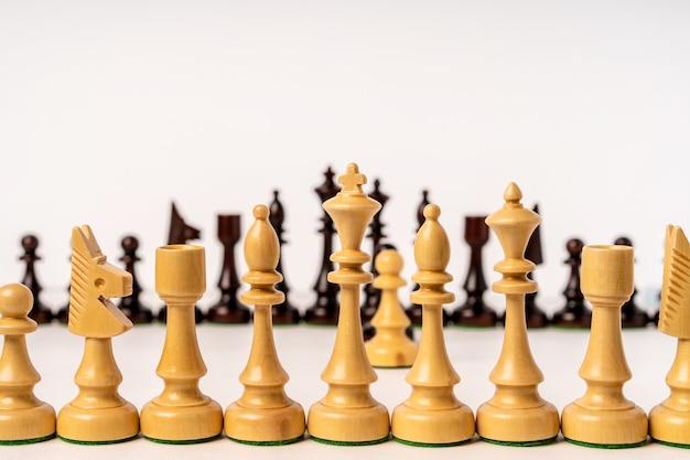 Righe di pezzi degli scacchi stanno l'una di fronte all'altra