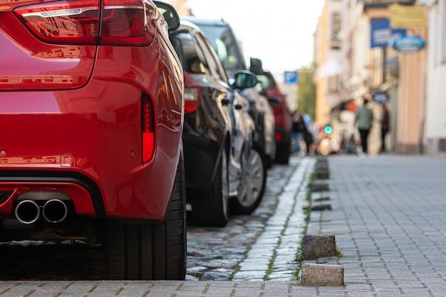File di diverse auto parcheggiate lungo la strada in città affollata