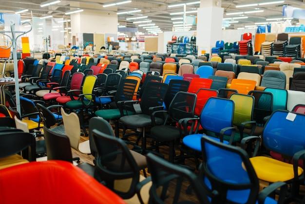 Righe di diverse sedie da ufficio nello showroom del negozio di mobili, nessuno. campioni di sedili comfort in negozio, articoli per interni moderni