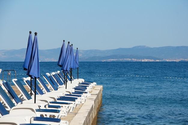 Righe vuote di chaise-longue sullo sfondo del mare, supetar, isola di brac, croatia