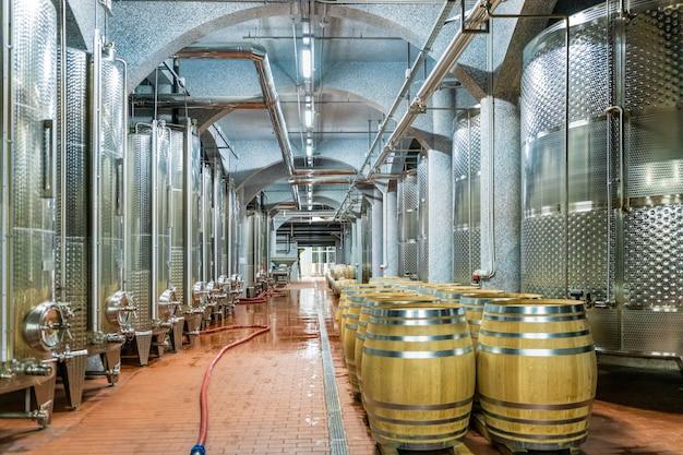 Filari di botti di rovere francese e inox in un moderno magazzino del vino