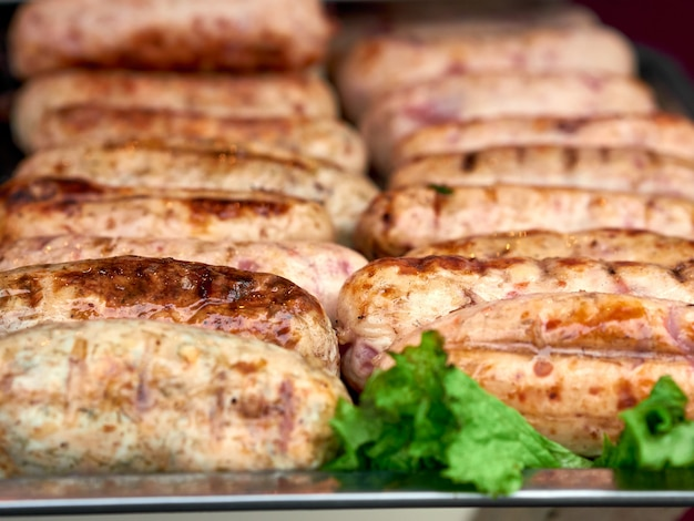 File delle salsiccie di recente grigliate della carne di pollo sul vassoio con lattuga fresca