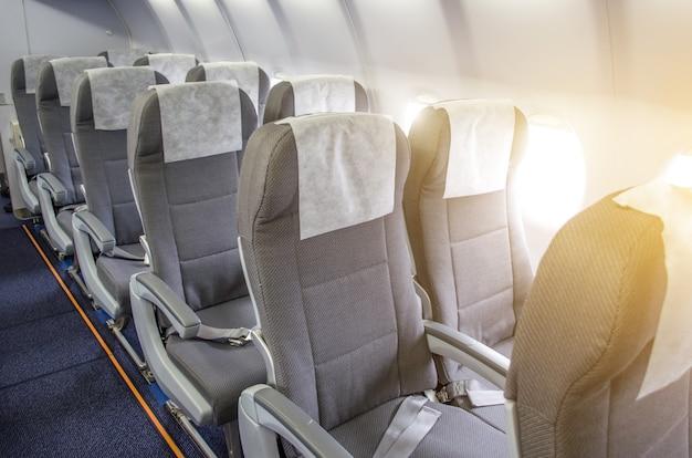 File di sedili passeggeri in aereo cabina.