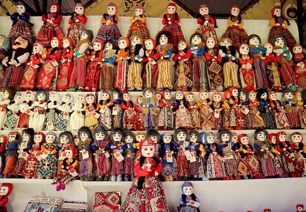 Righe di belle bambole in costumi tradizionali armeni per la vendita nel negozio di souvenir al mercato di vernissage, yerevan, armenia