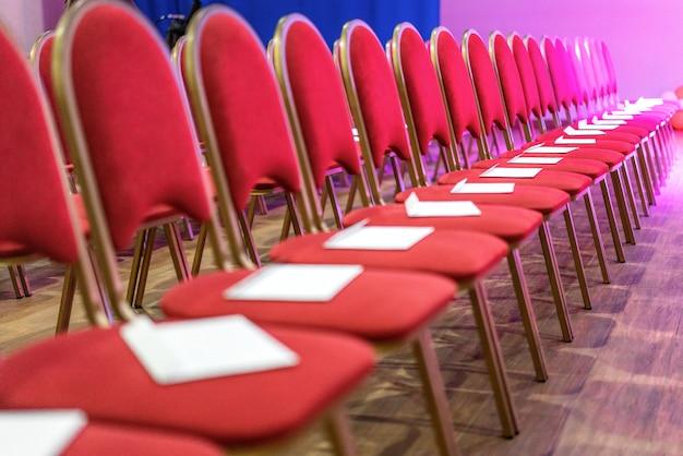 File delle sedie rosse nella sala per conferenze, nella riunione vuota o nella sala per eventi. posti ospiti vuoti.