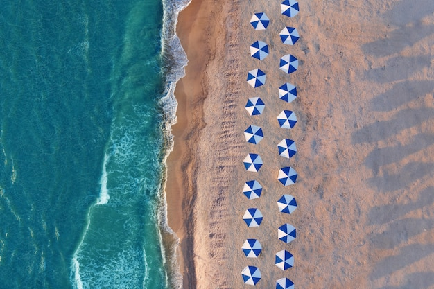 File di ombrelloni su una spiaggia deserta Foto Premium