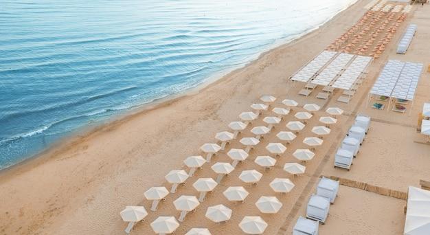 File di ombrelloni su una spiaggia deserta