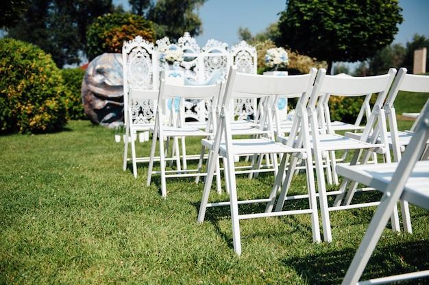 File delle sedie pieghevoli bianche su prato inglese