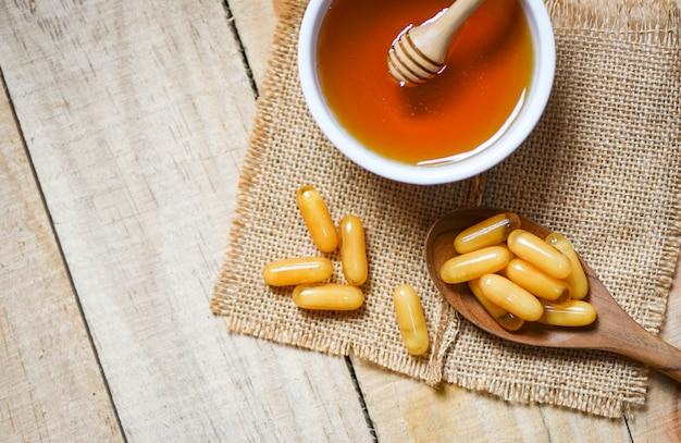 Capsule di gelatina reale in cucchiaio di legno sul sacco e miele in tazza