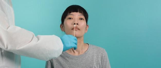 Test pcr rt. donna con tampone covid 19. test del coronavirus durante l'epidemia. medico che preleva il campione per il test del virus. sfondo verde blu. medico nel test del tampone della tuta dpi. test rapido dell'antigene del virus.