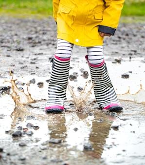 Stivali di gomma in una pozzanghera in procinto di saltare con spruzzi d'acqua da vicino.