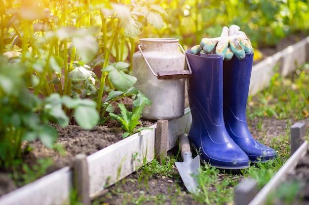 Stivali di gomma paletta e attrezzi dopo il giardinaggio tra i letti