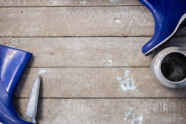 Stivali di gomma scoop e strumenti sullo sfondo di vecchie tavole flatlay