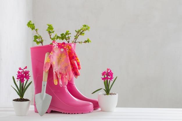 Stivali di gomma e fiori della molla sulla parete bianca