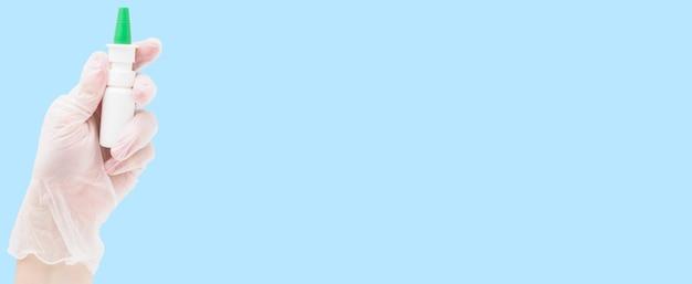 Una mano guantata di gomma tiene uno spruzzo di medicina fredda su sfondo blu. banner