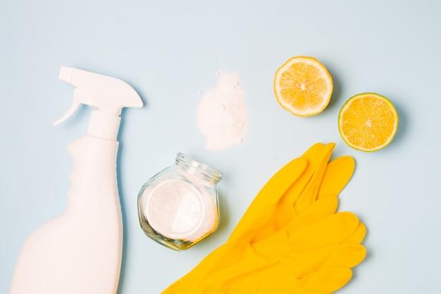 Guanti di gomma, una bottiglia di spray bianca senza etichetta, mezzo limone e lime, soda versata e un barattolo di vetro di soda