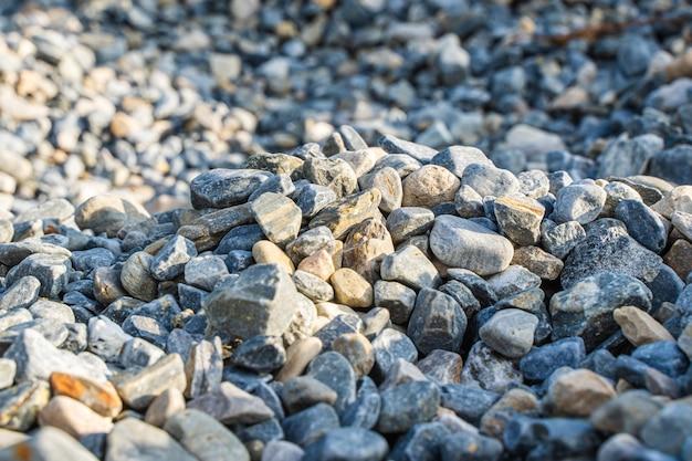 Fondo di macerie o ghiaia, materiale da costruzione. mucchio di molte piccole pietre, foto d'archivio