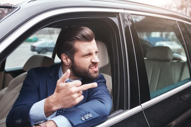 Uomo d'affari maleducato arrabbiato e maleducato uomo d'affari barbuto in abbigliamento formale sta gesticolando e facendo a