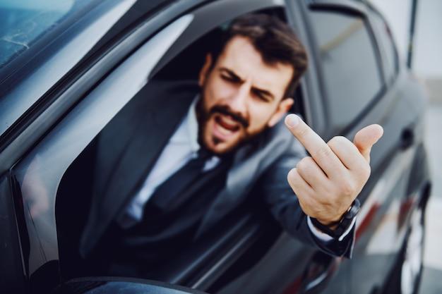 Uomo d'affari barbuto caucasico maleducato alla guida della sua auto e mostrando il dito medio ad altri conducenti.