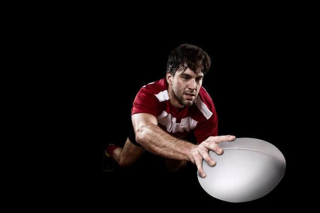 Giocatore di rugby in uniforme rossa. muro nero