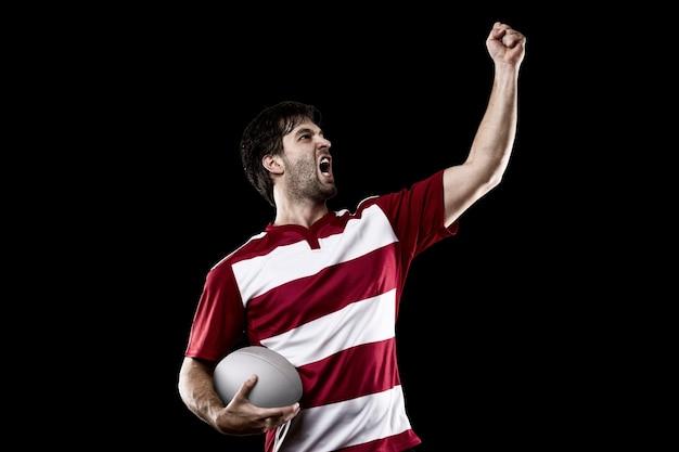 Giocatore di rugby in uniforme rossa che celebra. muro nero