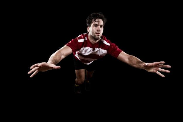 Giocatore di rugby in uniforme rossa che dà un placcaggio. muro nero