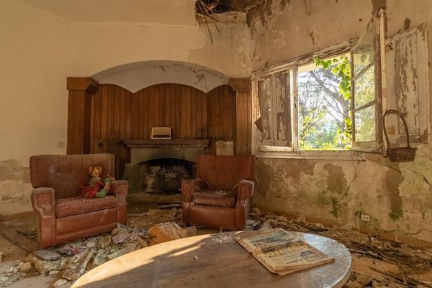 Soggiorno rovinato con camino in una casa abbandonata