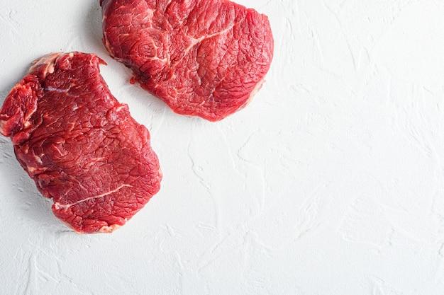 Bistecca di manzo, carne di manzo cruda biologica dell'azienda agricola fondo strutturato bianco. spazio vista dall'alto per il prezzo.