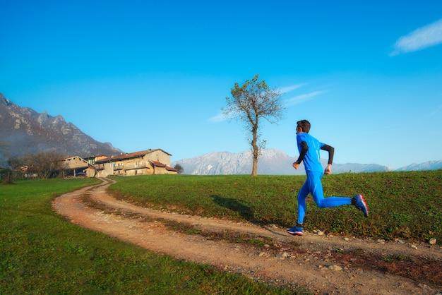 Addestramento professionale dell'atleta del corridore su una sporcizia della montagna