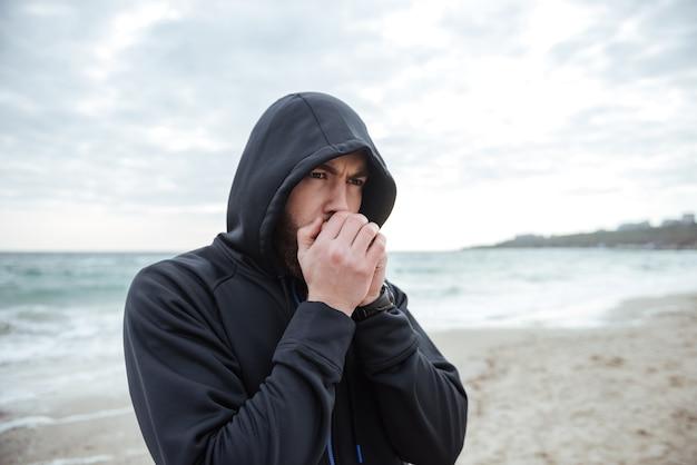 Corridore sulla vista laterale della spiaggia così freddo?