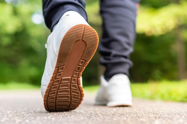 Piedi del corridore che corrono sul primo piano della strada sulle scarpe. uomo fitness sunrise jogging allenamento welness concept.