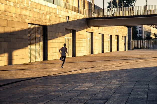 Corridore che fa jogging e si allena esercitando potenza camminando all'aperto in città