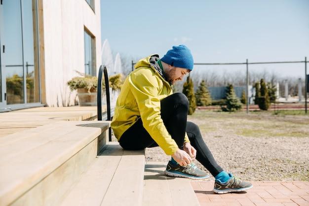 Uomo del corridore che lega i lacci delle scarpe su scarpe da ginnastica che si siedono sulle scale di legno che si preparano a correre la mattina