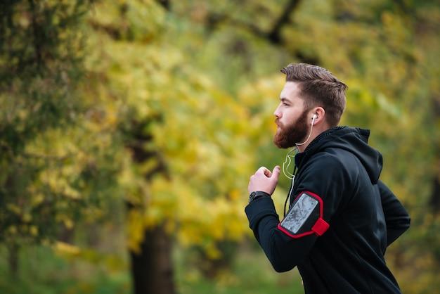 Corridore nel parco nella foto di moda del profilo