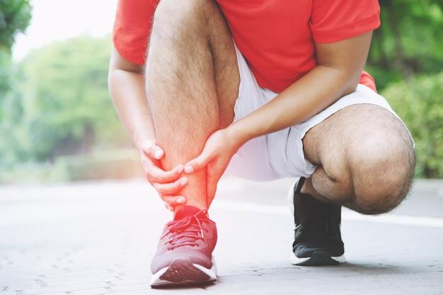 Corridore che tocca la caviglia attorcigliata o rotta dolorosa. incidente di formazione corridore atleta. lo sport in esecuzione distorsione alla caviglia provoca lesioni al ginocchio. e dolore alle ossa delle gambe. metti a fuoco le gambe rosse per mostrare dolore.