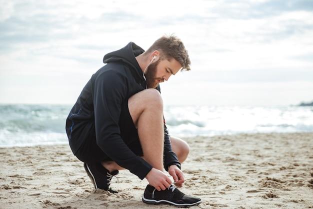 Corridore che allaccia i lacci delle scarpe sulla vista laterale della spiaggia